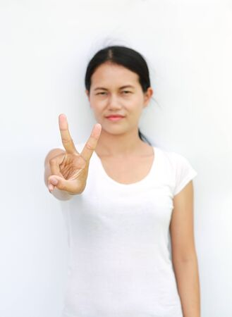 Young asian woman in T-Shirt Showing expression a two-finger victory, Selected focus at her finger