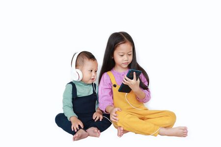 Adorable Asian older sister and little brother sharing to enjoys listening music with headphones by smartphone isolated over white background. Sharing concept.
