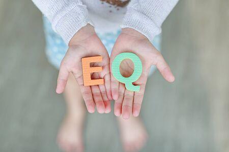 EQ (Emotional Quotient) sponge text on child hands. Education and development concept.