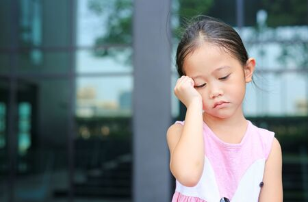 Serious little girl with posture her hand on cheek.