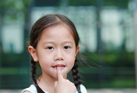 Asian little girl licking her fingers outdoor.