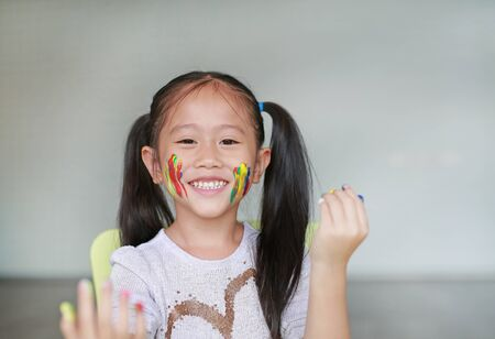 Portrait of smiling little girl looking through her colorful hands and cheek painted in kids room. Focus at face.