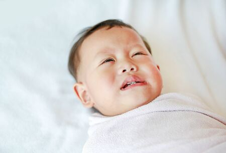 Close up Infant baby boy crying and screaming lying on bed.