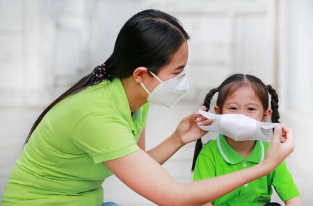 Asian young mother wearing protective mask for her daughter while outside to against PM 2.5 air pollution in Bangkok city. Thailand. Stock Photo