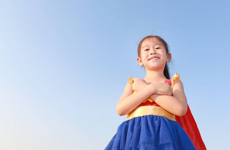 Little child girl Superhero on clear blue sky background. Kid super hero concept. 免版税图像