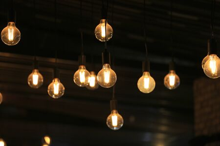 Vintage glowing light bulbs hanging. Decorative antique style light bulbs.