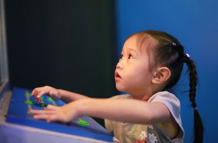 Close-up little Asian child girl playing arcade video game.