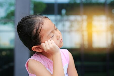 Unhappy little child girl with posture her hand on cheek. Stock Photo