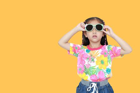 Cute little Asian kid girl wearing a flowers summer dress and sunglasses isolated on yellow background with copy space. Summer and fashion concept. Foto de archivo