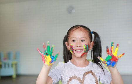 Happy little Asian girl with her colorful hands and cheek painted in the children room. Focus at baby face. 写真素材