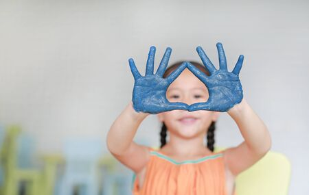 Portrait of smiling little girl looking through her blue hands painted in kids room. Focus at baby hands. Stockfoto