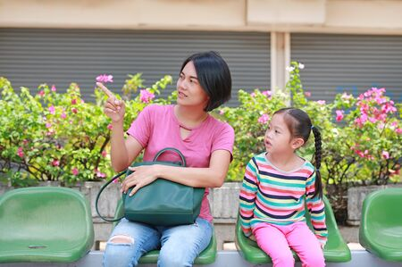 Asian mom and her daughter sitting on public transport bus. Mom pointing something to child girl looking.