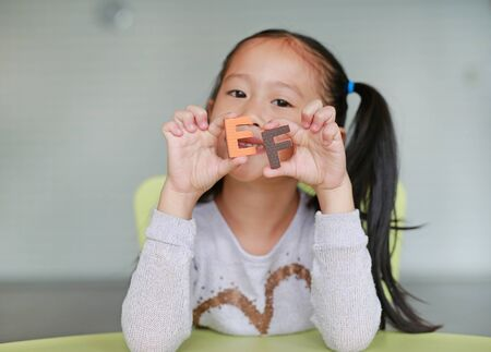 Happy little Asian child girl holding alphabet EF (Executive Functions) text on her face. Education and development concept. Stock Photo