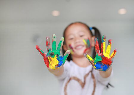 Happy little Asian girl with her colorful hands and cheek painted in the children room. Focus at baby hands. Stockfoto