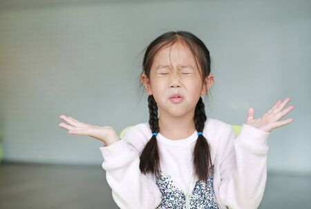 Angry little Asian child girl in classroom. Not listening. Sign and gesture concept. Stock Photo