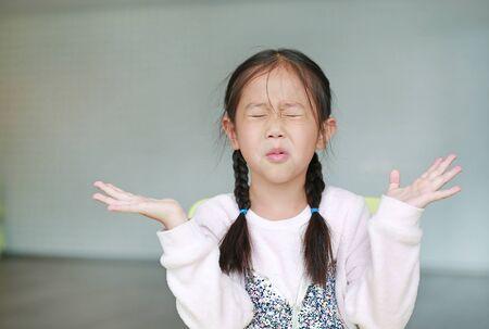 Niña niño asiático enojado en el aula. No escuchar. Concepto de signo y gesto.