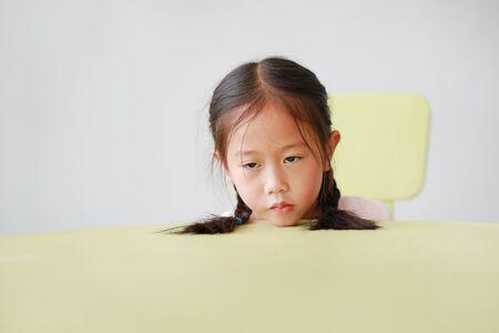 Sleepy little Asian child girl put head on table in classroom against white background. Tired Schoolgirl at desk. Reklamní fotografie