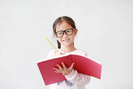 Happy little Asian child girl wearing eyeglasses and hold a book and write with pencil on white background. 스톡 콘텐츠