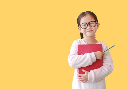 Portrait of smiling Asian schoolgirl wearing eyeglass hug a book and holding pencil in hand isolated over yellow background with copy space.