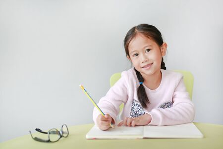 Smiling little Asian child girl writes in a book or notebook with pencil on table in classroom against white background. Portraits of kid looking straight at camera.