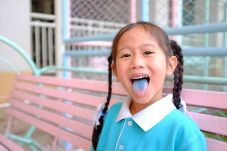 Cheeky funny face little Asian child girl smile and poking out blue colored tongue. Food coloring in children sweets. Foto de archivo