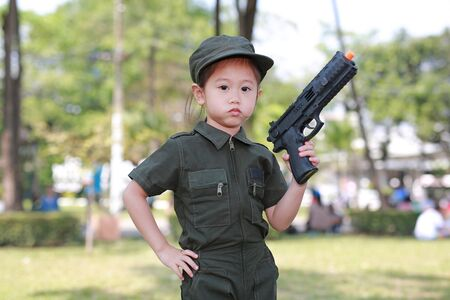 Asian child girl in pilot soldier suit costume with shooting gun up. Dream job concept.