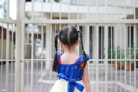 Closeup Child girl holding steel fence. Rear view.