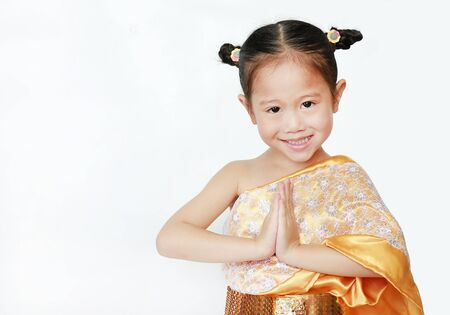 Portrait of asian child girl in traditional thai dress praying isolated on white background. (Sawasdee is meaning hello)