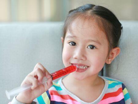 Happy little Asian child girl feeding liquid medicine with a syringe by self.