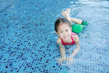 Adorable little Asian child girl wear mermaid swimming suit has fun at the pool.