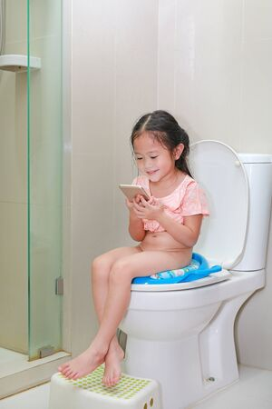 Adorable little Asian child girl playing smartphone while sitting on toilet.