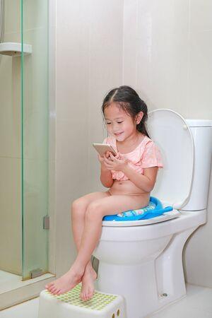 Entzückendes kleines asiatisches Kindermädchen, das Smartphone beim Sitzen auf der Toilette spielt.