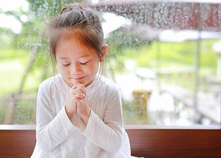 Adorable little Asian girl praying at glass windows on the raining day. Spirituality and religion.