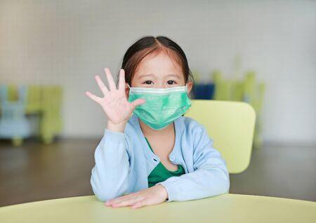 Kleines asiatisches Kindermädchen, das eine Schutzmaske trägt und fünf Finger zeigt, die auf einem Kinderstuhl im Kinderzimmer sitzen.