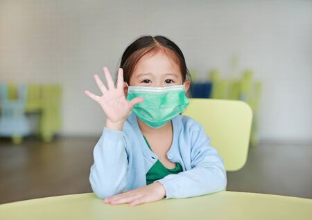 Little Asian child girl wearing a protective mask with showing five fingers sitting on kid chair in children room. Foto de archivo