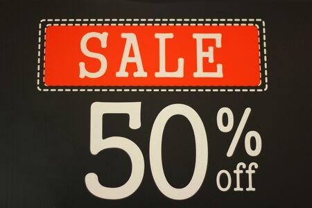 Sale 50% off sign on black background.