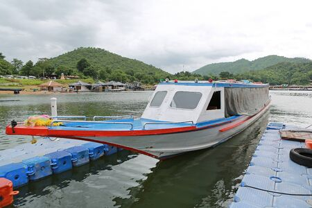 Thai boat floating on river and bungalows floating on river at kanchanaburi, Thailand.