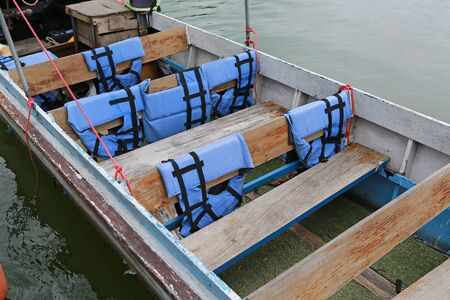 Close-up long-tailed boats on river with life jackets hanging.