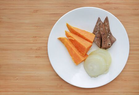 Raw of boiled meat and vegetables baby food (pork liver, onion and sweet potato) in white plate on wooden board. Фото со стока