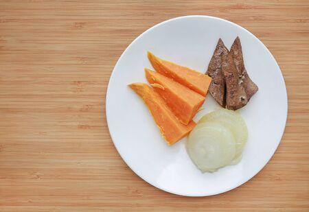 Rohes gekochtes Fleisch und Gemüse Babynahrung (Schweineleber, Zwiebel und Süßkartoffel) in weißer Platte auf Holzbrett. Standard-Bild