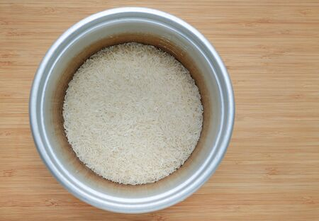 Raw Thai local jasmine rice in pot on wood background ready for cooking.