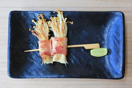 Bacon and Enoki Mushroom roll stick served with lemon on black plate on wood table. Japanese cuisine food. Archivio Fotografico
