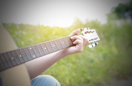 Hand playing on acoustic guitar in the nature. Stock Photo