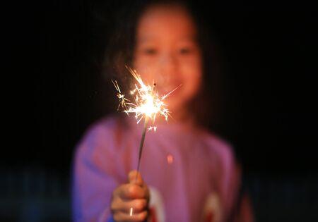 Little Asian child girl enjoy playing firecrackers. Focus at fire sparklers. Standard-Bild