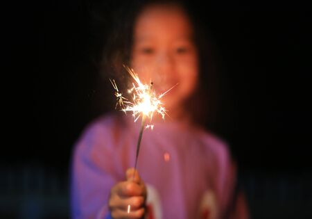 Little Asian child girl enjoy playing firecrackers. Focus at fire sparklers. Foto de archivo