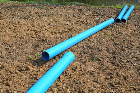 PVC water pipe waiting for connections on dry soil.