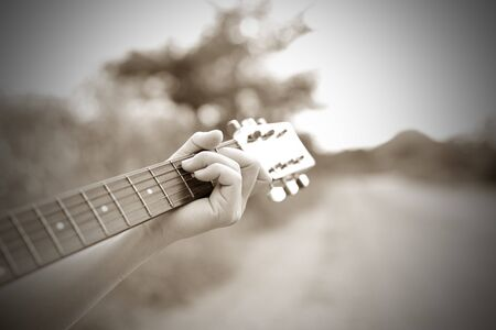 Close-up male hand playing on acoustic guitar outdoor. Vintage tone. Stock Photo