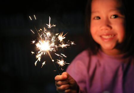 Little Asian child girl enjoy playing firecrackers. Focus at fire sparklers. Фото со стока
