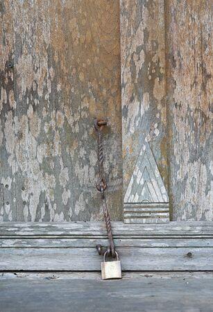 An antique door locked with key.