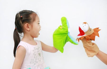 Little Asian child girl hands playing animal puppets with hand of her mother on white background. Educations concept. 版權商用圖片